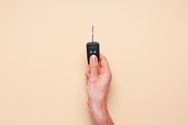 La mano maschio tiene le chiavi della macchina su fondo beige. concept car, noleggio auto, regalo, lezioni di guida, patente di guida. vista piana laico e dall'alto