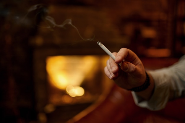 La mano maschio tiene una sigaretta, interno ricco dell'ufficio con il camino. cultura del fumo di tabacco, sapore specifico. svaghi del fumatore a casa