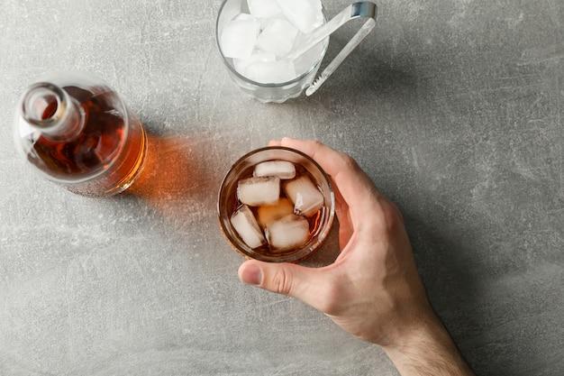 La mano maschio tiene il bicchiere di whisky su sfondo grigio con bottiglia e cubetti di ghiaccio, vista dall'alto