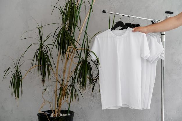 La mano maschile tiene il gancio con una maglietta bianca vuota, primo piano