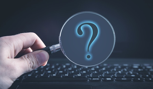 La mano maschio tiene una lente d'ingrandimento e un punto interrogativo sulla tastiera del computer.