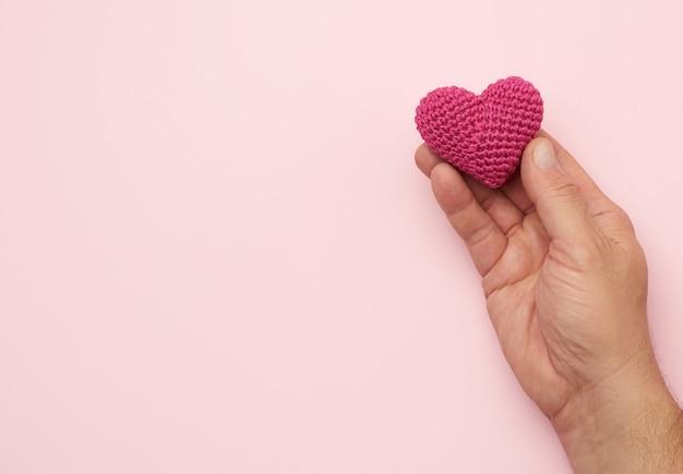 La mano maschio tiene il cuore rosso della tessile