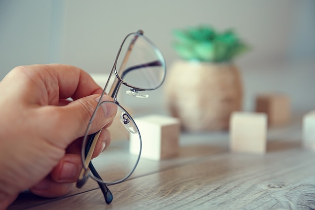 La mano maschio tiene gli occhiali dalla montatura sottile e poggia su un tavolo di legno