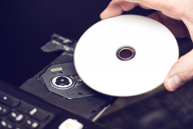Mano maschio che inserisce un dvd in un'unità disco