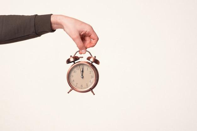 La mano maschile tiene in mano una sveglia su uno sfondo bianco caldo.