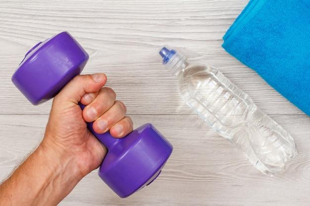 La mano maschile tiene in mano un manubrio in camera o in palestra con una bottiglia d'acqua e un asciugamano sullo sfondo. strumenti per il fitness. vista dall'alto