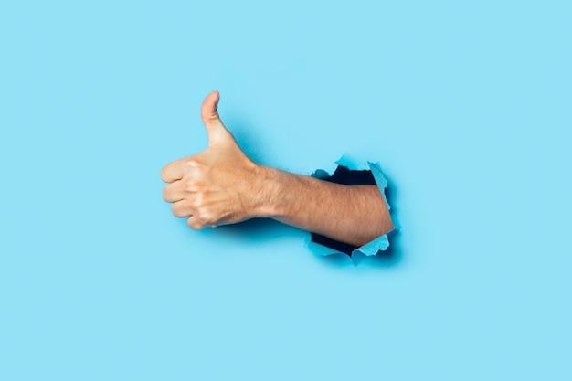 La mano maschio fa un gesto della mano sull'azzurro