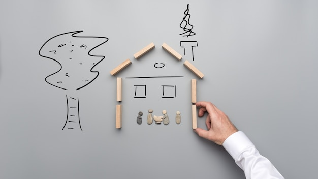 Mano maschio che fa una casa di pioli di legno per riparare una famiglia fatta di ciottoli. su sfondo grigio con alberi disegnati a mano e dettagli della casa.