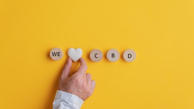 Mano maschile che fa un segno we love cbd scritto su cerchi di legno tagliati con marmo a forma di cuore nel mezzo.