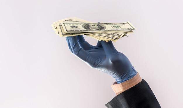 La mano maschile nel guanto medico ci tiene isolate le banconote per la protezione contro il covid-19 (coronavirus).