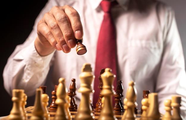 Pedone in movimento mano maschio sulla scacchiera, gioco di partenza. concettuale
