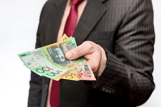 La mano maschio che offre le banconote del dollaro australiano ha isolato e