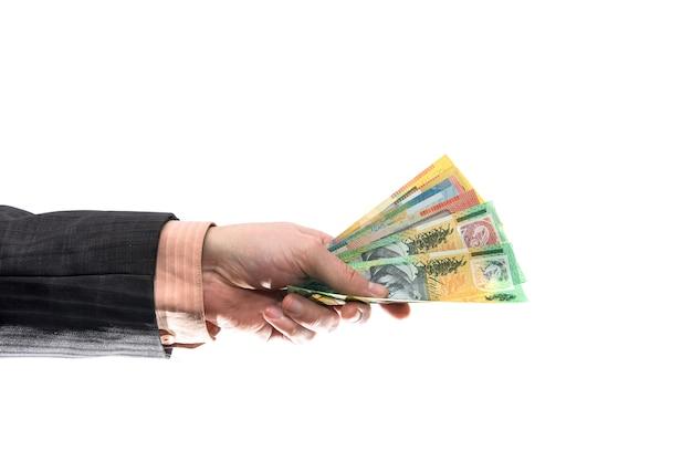 Mano maschio che offre banconote del dollaro australiano isolate su bianco
