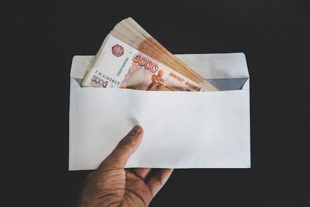 Mano maschile che apre una busta bianca piena di valuta russa rublo russo, rub sul tavolo di legno come simbolo di trasferimento di denaro, riciclaggio di denaro o corruzione in russia
