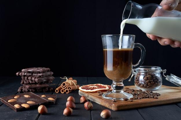 Mano maschio che versa il latte nel bicchiere di caffè nero con cioccolato, bastoncini di cannella e fette di pompelmo essiccato su sfondo nero vista laterale.