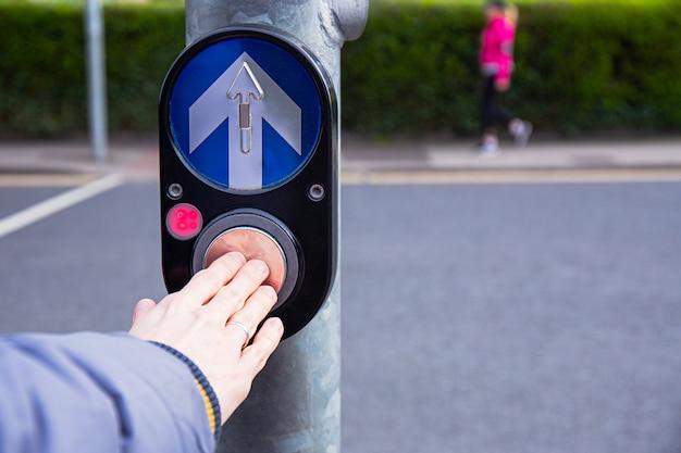 Mano maschio che spinge il pulsante per il semaforo. usa i semafori agli incroci. il pulsante del meccanismo accende i semafori sulla strada. chiusura intersezione semaforica controllo sistema.