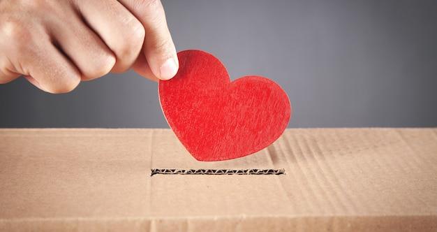 Mano maschio che mette cuore rosso in scatola.