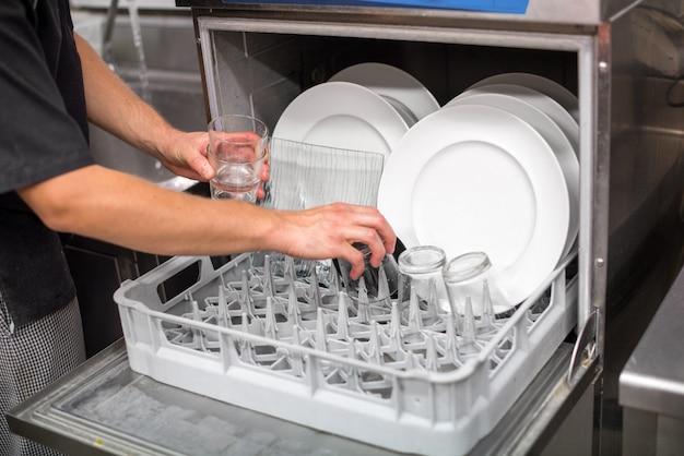 Mano maschio che rimuove i piatti puliti da una lavastoviglie