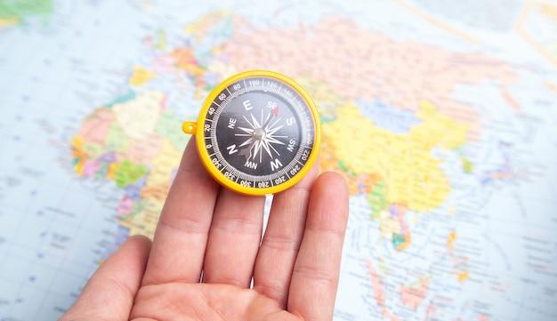 Mano maschio che mostra la bussola sullo sfondo della mappa del mondo.