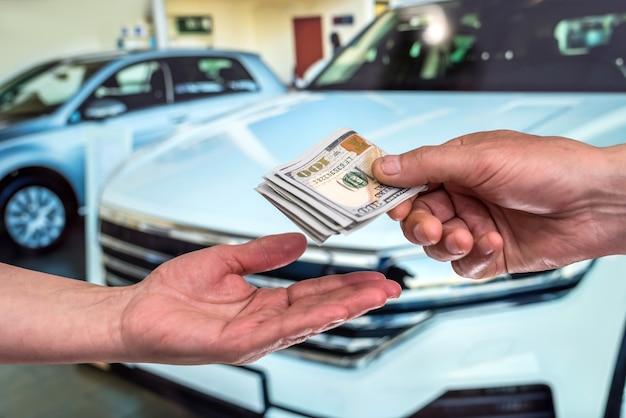 Mano maschio che mostra un dollaro per l'acquisto di un'auto in autohouse. finanza