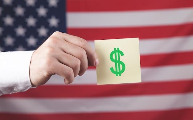 Mano maschio che mostra il simbolo del dollaro in una nota adesiva