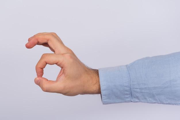 Mano maschio che mostra un segno giusto con le dita. ok gesto su uno spazio bianco.