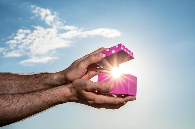 Mano maschio che mostra scatola regalo rosa con sfondo azzurro del cielo. il giorno di san valentino concetto. piccole scatole regalo fatte a mano nella notte blu brillante.