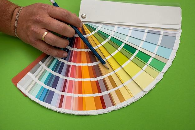 La mano maschio mostra campioni colorati isolati su sfondo verde. avvicinamento
