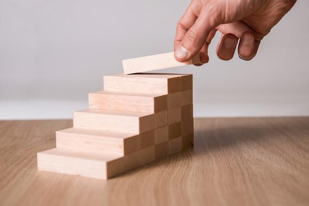 Mano maschio che impila i blocchi di legno. sviluppo aziendale e concetto di crescita