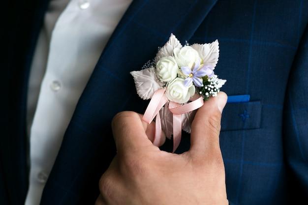 La mano maschile raddrizza il fiore all'occhiello del vestito dello sposo.