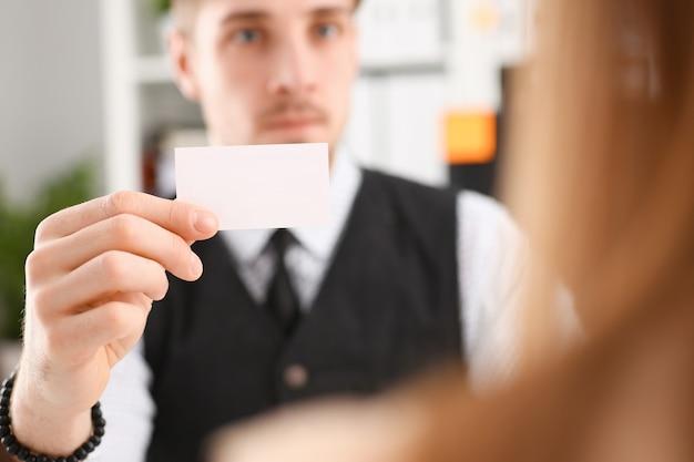 La mano maschile in tuta dà un biglietto da visita vuoto al visitatore