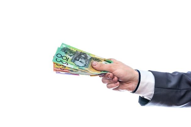 Mano maschio con dollari australiani isolato sul muro bianco