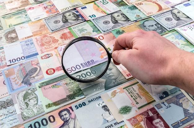 Mano maschio con lente di ingrandimento che controlla le banconote del mondo