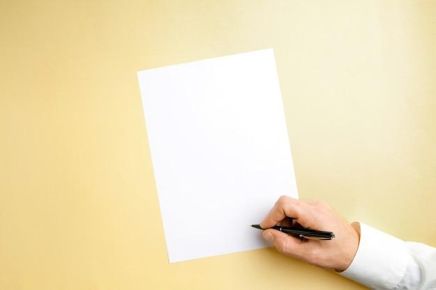 Mano maschile con penna e scrittura su foglio vuoto sul muro giallo.