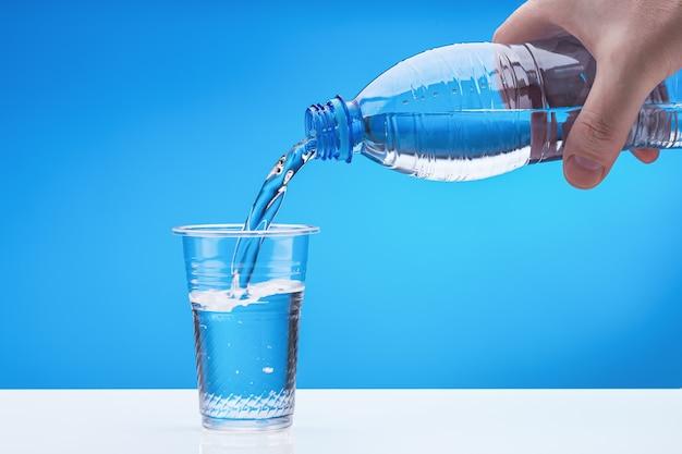 Mano maschio con bottiglia di plastica. l'acqua si riversa nel bicchiere. copia spazio.