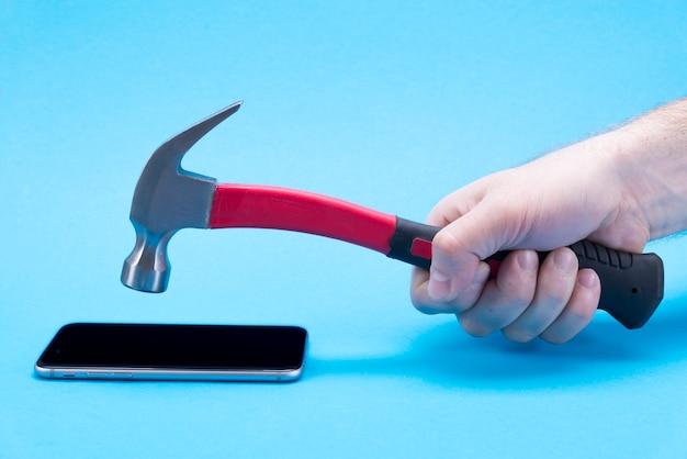 La mano maschio con un martello rosso rompe un telefono cellulare