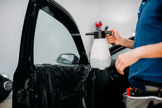 Mano maschile con spray, processo di installazione della tinta del finestrino dell'auto, procedura di installazione, pellicola oscurante