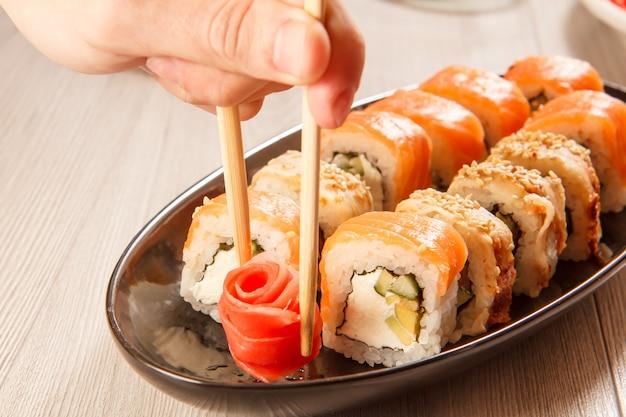 Mano maschio con due bacchette che tengono zenzero sottaceto sotto forma di rosa rossa e diversi involtini di sushi con riso, verdure, frutti di mare sullo sfondo
