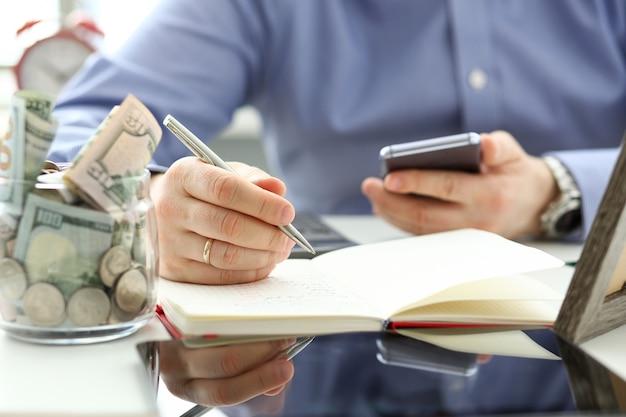 La mano maschio scrive qualcosa in blocco note con la penna d'argento mentre usa il suo telefono