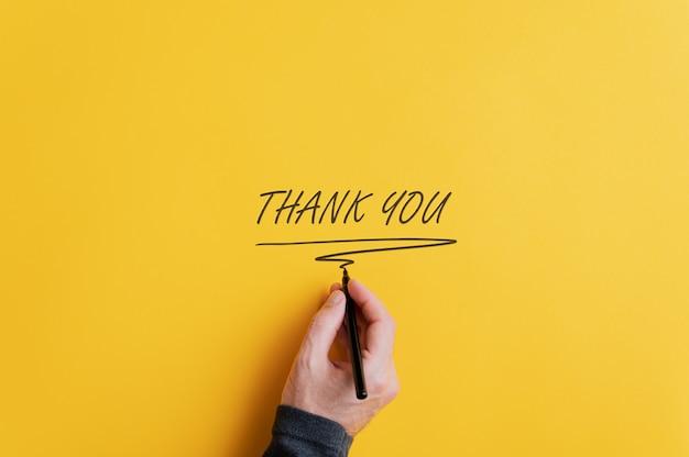 Mano maschio che scrive un segno di ringraziamento