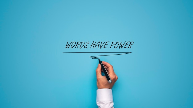 Mano maschile che scrive un segno di potere di parole con pennarello nero su sfondo blu.