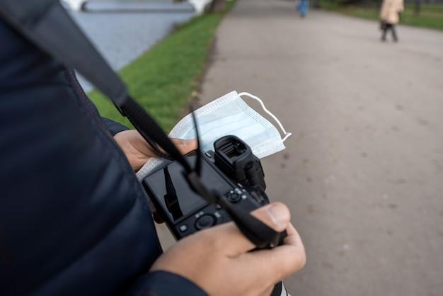 Le mani maschii stanno tenendo una fotocamera reflex digitale e una maschera medica