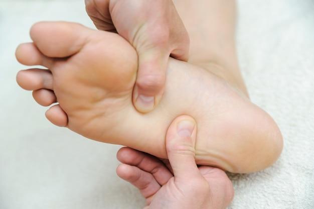 Le mani maschili massaggiano i piedi.