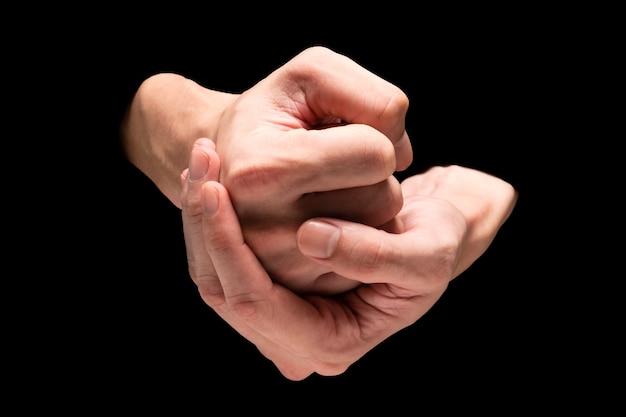 Mani maschili su sfondo nero.
