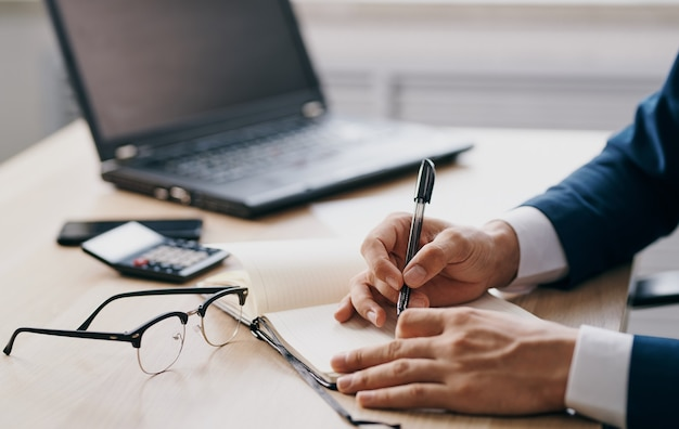 Il maschio passa i vetri dei documenti di finanza aziendale apre l'ufficio e il blocco note del computer portatile. foto di alta qualità