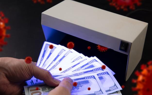 Mani maschili che controllano le banconote nel rilevatore, modelli 3d di coronavirus che si diffondono. l'alto rischio di infezione. pandemia, epidemia, vie di malattia e infermità che non vediamo nelle cose quotidiane.