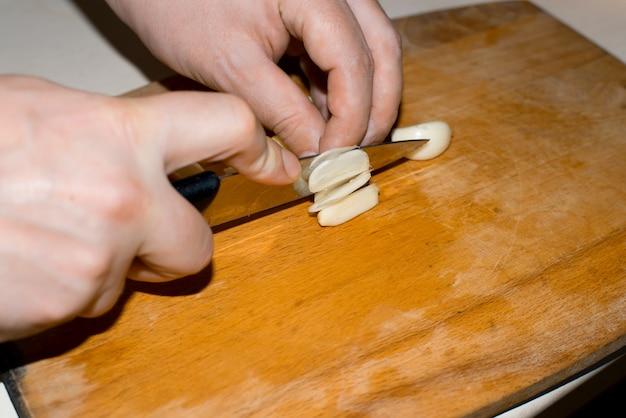 Le mani maschili tritano l'aglio sbucciato su un tagliere di legno, primo piano.