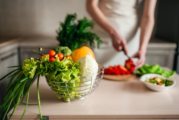 Mani maschii che tagliano insalata e cipolla, cucinando cibo sano in cucina.
