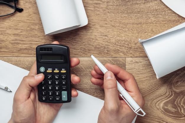 Le mani degli uomini contano sulla calcolatrice il costo di costruire una casa su un tavolo di legno.