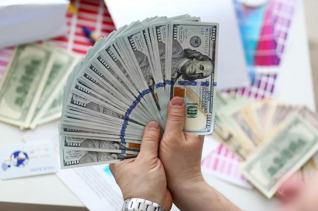 Mani maschili che contano soldi da un enorme pacco